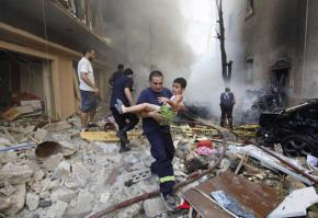 A rescue worker carries a child away from the scene of the car bomb attack in Beirut