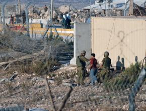 IDF soldiers interrogate a Palestinian youth at a West Bank checkpoint