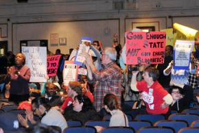 Parents and teachers at the PEP meeting protest the threatened closure of schools