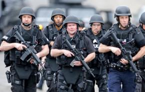 Heavily armed police move through residential streets in Watertown, Mass.