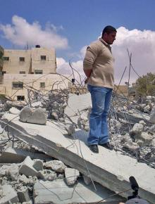 An earlier victim of home demolition stands on the remains of his house in east Jerusalem
