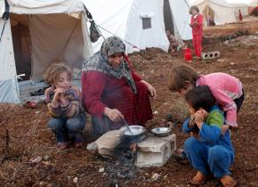 Refugees from the fighting in Syria prepare a meal outside their tent in a camp on the Syrian-Turkish border