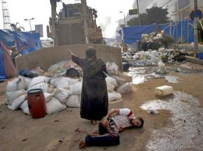 An Egyptian woman protects an injured youth from a security forces bulldozer dismantling a protest camp