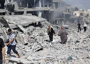 People walk through the rubble during a pause in the 2014 Israeli assault on Gaza