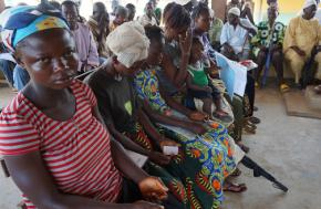 Residents of a quarantined community in Sierra Leone sit in a crowded treatment center