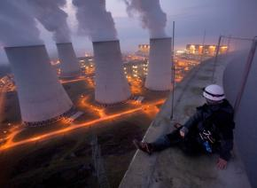A Greenpeace activists sits at the top of a power plant
