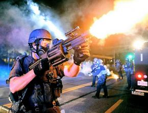 An officer in riot gear fires tear gas at protesters in Ferguson