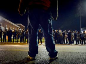 A protester faces down a line of riot police in Ferguson