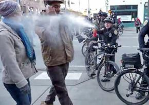 A Seattle police officer douses Jesse Hagopian (on phone) with pepper spray at point-blank range