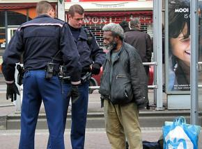 Two police officers harass a homeless man