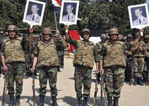 Syrian government troops pose with portraits of dictator Bashar al-Assad