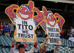 Cleveland Indians fans hold up cut-outs of the team mascot Chief Wahoo
