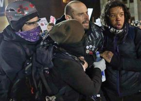 A wounded protester is helped away from a demonstration against far-right speaker Milo Yiannopoulos