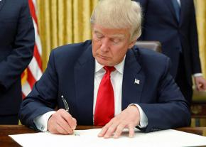 Trump signs an executive order on his first day in the Oval Office