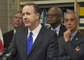 Chicago Public Schools CEO Forrest Claypool at the microphone, flanked by Mayor Rahm Emanuel and other officials