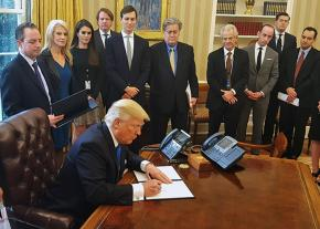 Trump signs an executive order surrounded by advisers and cabinet officials