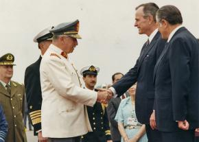Chilean dictator Augusto Pinochet exchanges greetings with then President George H.W. Bush