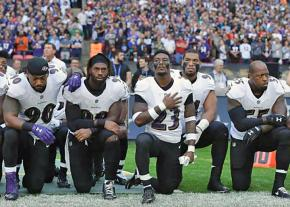 Members of the Baltimore Ravens kneel in protest during the National Anthem