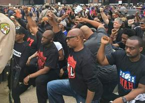 Anti-racist activists take a knee in solidarity outside the Baltimore Ravens stadium