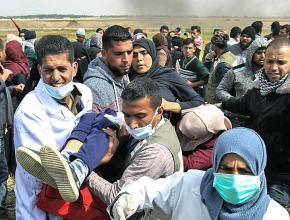 Medics rush to treat a Palestinian woman wounded by Israeli snipers during demonstrations in Gaza