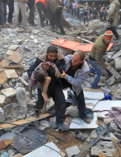 Gaza residents carry a child away from the site of an Israeli strike