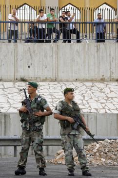 Hezbollah supporters look on as Lebanese army soldiers clear roadblocks along the highway leading to Beirut's airport. (Patrick Baz | AFP)