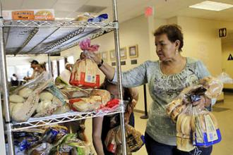 A woman sorts through a rack of breads and buns at a food pantry in San Jose, Calif.