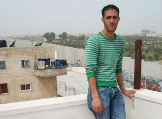 Bilal Jadou inside the Aida refugee camp, overlooking the separation wall and his home on the other side (Nora Barrows-Friedman)