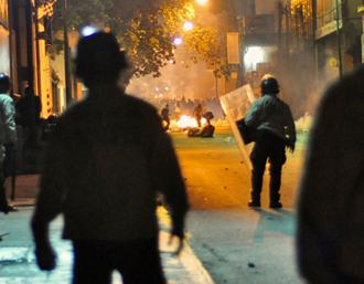 Police look on as right-wing protesters set a fire in a Caracas street  (Andrés E. Azpúrua)