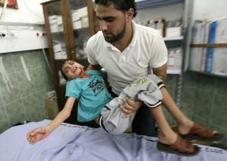 A Palestinian man brings a wounded child into a hospital