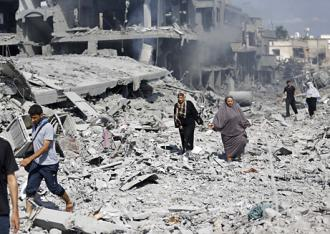 People walk through the rubble during a pause in the 2014 Israeli assault on Gaza (Iyad al Baba)