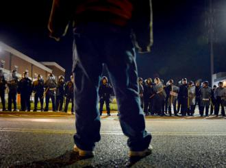 A protester faces down a line of riot police in Ferguson (Hans Peter Meyer)