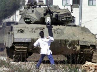 Faris Odeh throws a stone at an Israeli tank ten days before he was gunned down in Gaza
