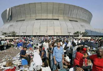 New Orleanians sit outside the Superdome waiting to get a space inside