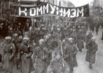 "Members of the Red Guard march under the banner of ""Communism"" following the 1917 Russian Revolution"