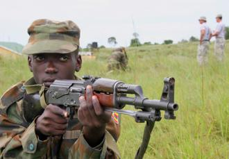 "Ugandan troops on training exercises as U.S. ""advisers"" look on in the background (Master Sgt. Ruby Zarzyczny)"