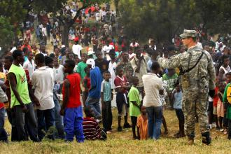 A U.S. soldier monitors a crowd of people waiting for aid in Haiti (Fred W. Baker III)