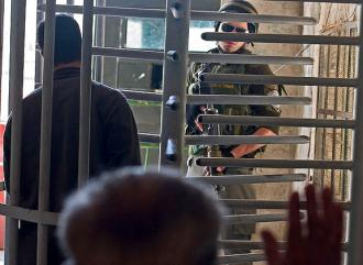 An Israeli soldier watches Palestinians passing through a West Bank checkpoint