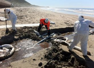 Clean-up workers contain an oil pipeline spill near Ventura, Calif. (U.S. Coast Guard)