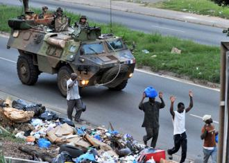 French troops roll through Abidjan in a tank