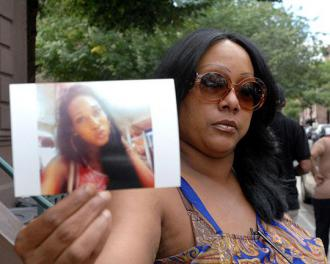 Islan's mother Dolores holds up her picture at a vigil (Islan Nettles Memorial page)
