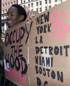 A participator in Occupy Wall Street publicizes the Occupy the Hood twitter feed (Bob Jagendorf)