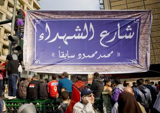 """Protesters hang a banner at the entrance to Mohammad Mahmoud Street renaming it """"Martyrs Street"""" (Hossam el-Hamalawy)"""