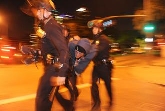 Police arrest an activist penned into the Occupy LA camp