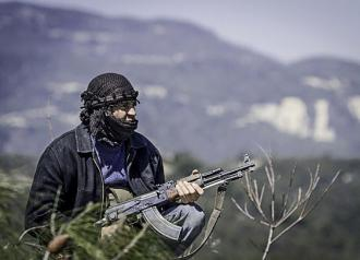 A Syrian rebel fighter holds a position during fighting near Idlib