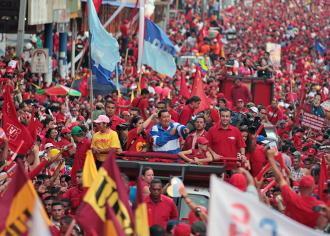 Hugo Chávez (in blue and white) joins in a mass rally in Caracas