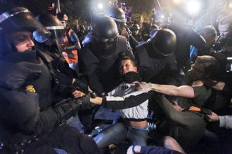 Spanish riot police attacking a protester in Madrid outside the parliament building