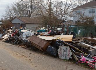 Debris piled outside storm-damaged homes on Staten Island (John De Guzmán)
