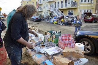 Residents in the Rockaways collect donated food items in a wreckage-strewn street (Karen Blumberg)