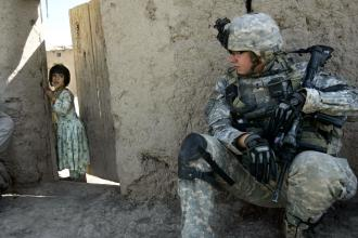 An Afghan girl looks on as U.S. troops carry out a mission